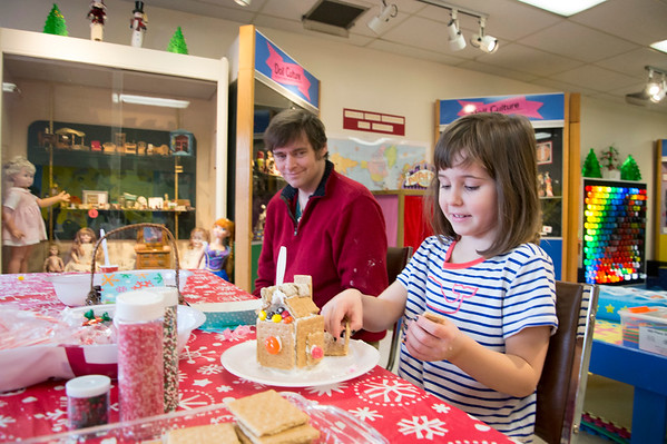 12/27/19 Wesley Bunnell | StaffrrGingerbread house making took place on Friday afternoon at the New Britain Youth Museum in New Britain. Neil McCarthy looks on as his daughter , Maeve age 6, works her house.