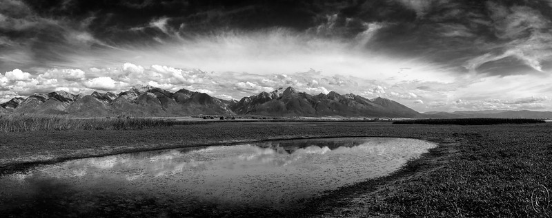 24 Nov 15.  Some of you may remember what I've written previously about the National Bison Range in western MT or the St Ignatius Chapel nearby. About 10 miles north of St Ignatius one finds the Ninepipe National Wildlife Refuge which is one of a group of four wildlife refuges of which the National Bison Range is a part all in close proximity to each other. This 4,000+ A refuge is one you will most likely drive right by and never find unless you have some form of locator device as it is almost unmarked and the parking lot for it is little more than a small patch of dirt and gravel with one covered reader board. There is a fence surrounding the area and you enter through a gate and then just walk around in what appears to be nothing but a big field. However first impressions here can be very misleading as after you've ambled a few hundred feet into the refuge you are met with an abundance of wet areas many of which are filled with water fowl ranging from ducks to herons to pelicans of all things. And that is just the beginning. The image for today does not feature any of the wildlife, but it will give you a small inkling of the beauty to be found there.  Five different frames were stitched together to create the base image which was first adjusted for max tonality, then given a slight enhancement to the sky to bring it out, and finally converted to a B&W image.  Nikon D300s; 18 - 200; Aperture Priority; ISO 200; 1/800 sec @ f / 8.