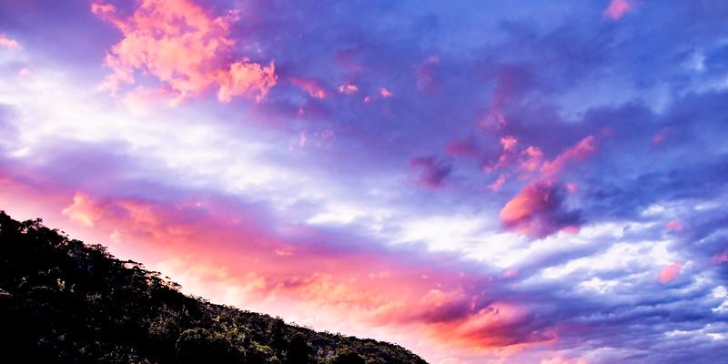 Hot pink colored cumulus cloud, sunset seascape.