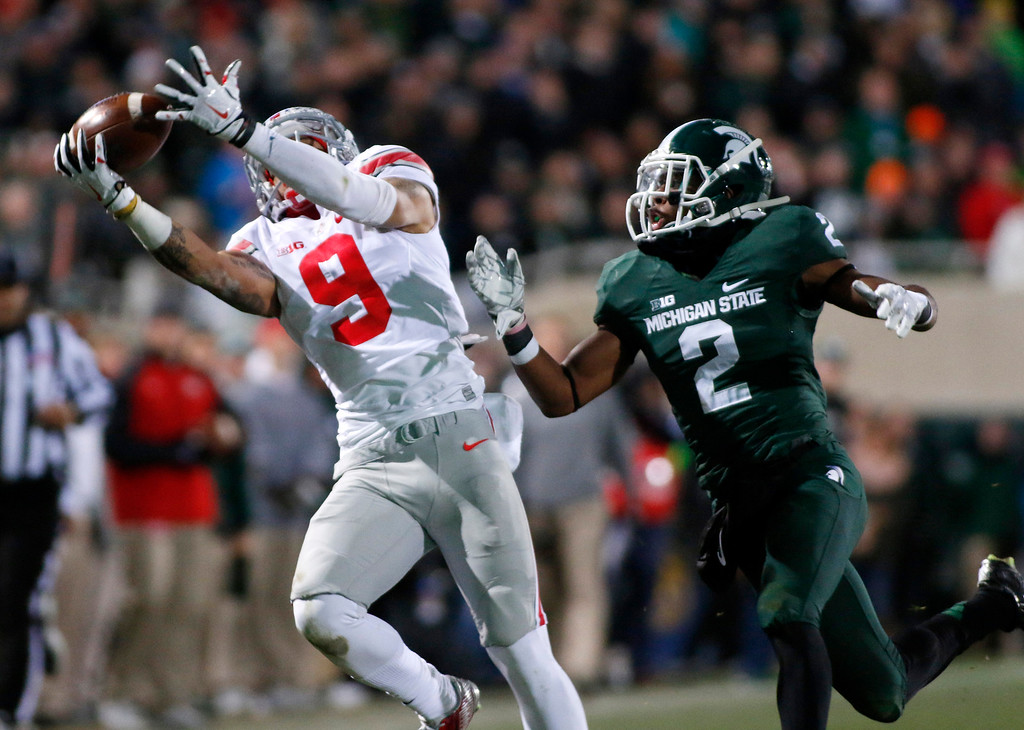 . Ohio State receiver Devin Smith (9) pulls in a 43-yard pass against Michigan State\'s Darian Hicks (2) during the second quarter of an NCAA college football game, Saturday, Nov. 8, 2014, in East Lansing, Mich. (AP Photo/Al Goldis)