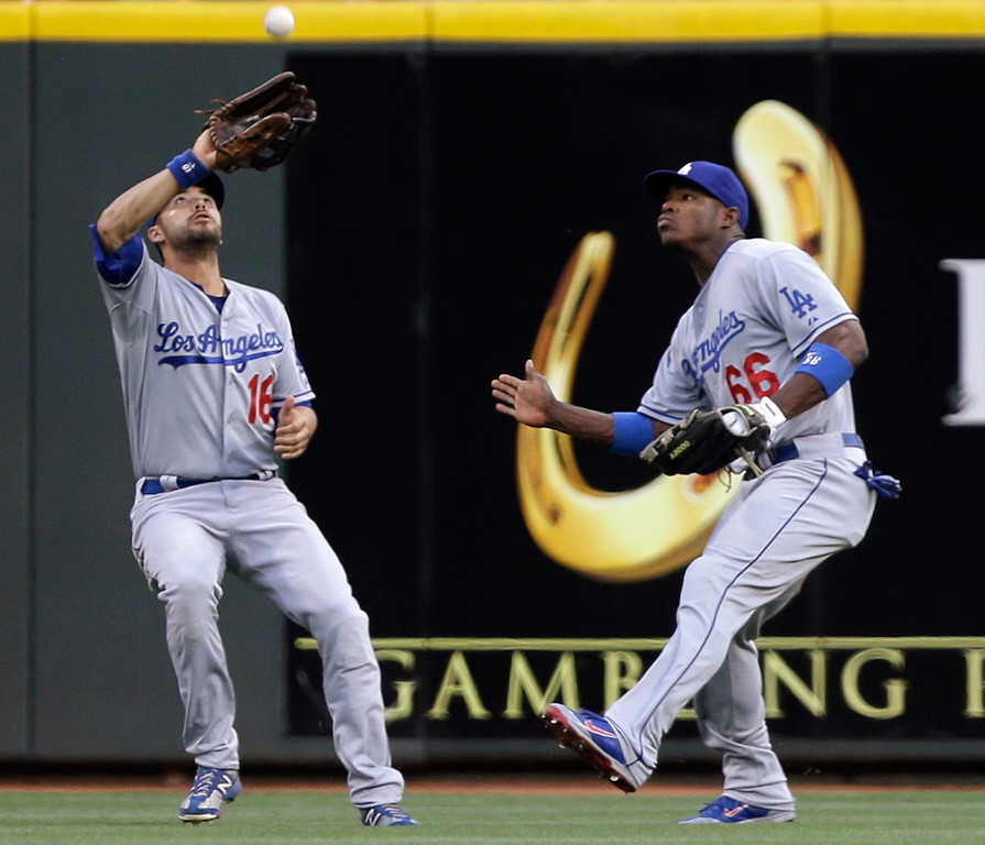 . Los Angeles Dodgers center fielder Andre Ethier (16) catches a fly ball hit by Cincinnati Reds\' Jay Bruce, next to right fielder Yasiel Puig in the first inning of a baseball game, Friday, Sept. 6, 2013, in Cincinnati. (AP Photo/Al Behrman)
