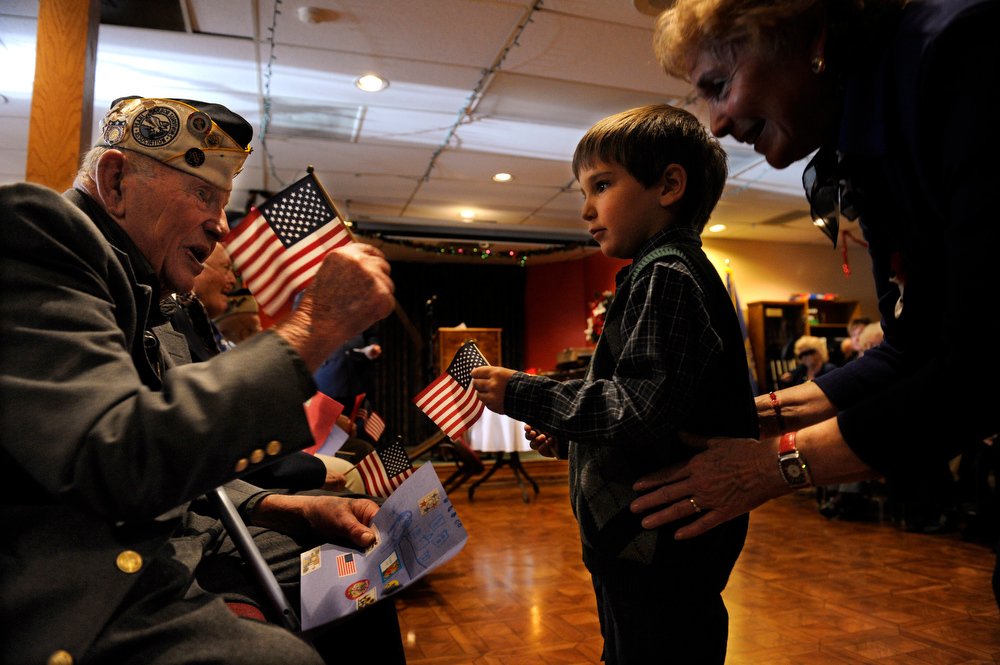. Anthony Villano, 4, presents George Richard, left, and the rest of the veterans with an American flag. The American Legion Post 1 in Denver hosts a Remember Pearl Harbor 71st Anniversary Program on Friday, Dec. 7, 2012, honoring the survivors, their wives, and the widows. Kathryn Scott Osler, The Denver Post