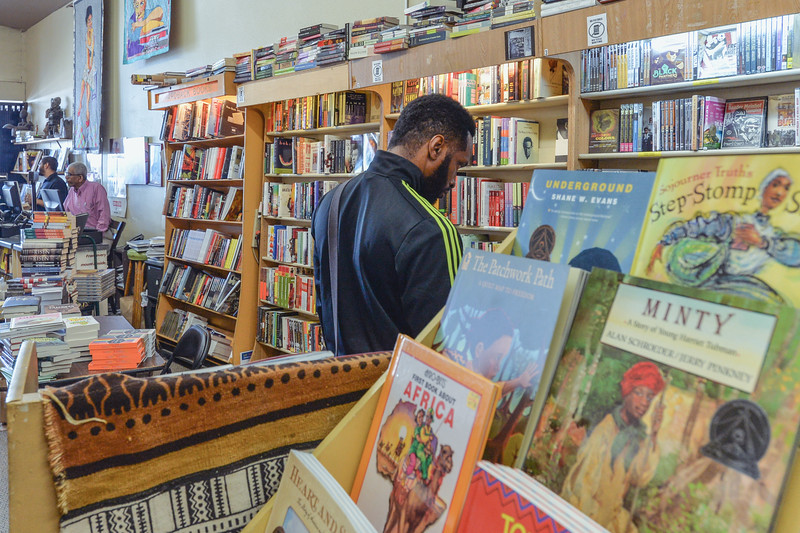 Customer perusing at Eso Won Books in Leimert Park Village.