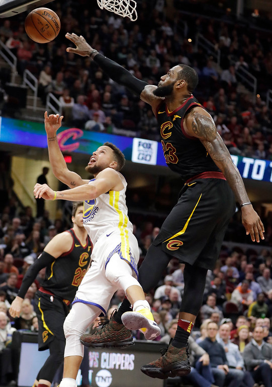 . Cleveland Cavaliers\' LeBron James blocks a shot by Golden State Warriors\' Stephen Curry, left, in the second half of an NBA basketball game, Monday, Jan. 15, 2018, in Cleveland. (AP Photo/Tony Dejak)