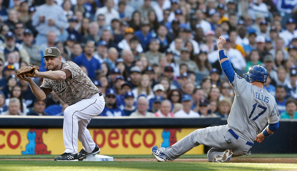 . Los Angeles Dodgers\' A.J. Ellis is frced oput at third as San Diego Padres third baseman Chase Headley takes in the throw on a failed sacrifice bunt attempt in the fifth inning of the opening game of Major League baseball in the United States Sunday, March 30, 2014, in San Diego.  (AP Photo/Lenny Ignelzi)