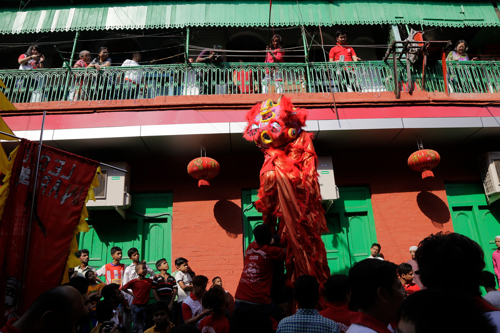 . Ethnic Chinese residents from a balcony watch lion dancers on the first day of Lunar New Year in Kolkata, India, Friday, Feb. 16, 2018. People in Asia and around the world are celebrating the Lunar New Year on Friday with festivals, parades and temple visits to ask for blessings. This year marks the year of the dog, one of the 12 animals in the Chinese astrological chart. (AP Photo/Bikas Das)