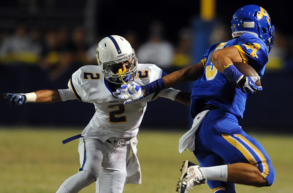 . Bishop Amat\'s Anthony Camargo (C) (5) runs past Charter Oak\'s Candy Nava (2) in the first half of a prep football game at Bishop Amat High School in La Puente, Calif. on Friday, Sept. 20, 2013.    (Photo by Keith Birmingham/Pasadena Star-News)