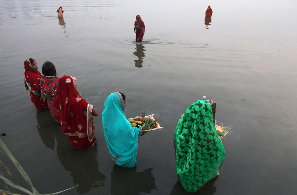 . Indian Hindu devotees perform rituals at sunset during Chhath Puja festival in the Hussain Sagar Lake in Hyderabad, India, Friday, Nov. 8, 2013.  (AP Photo/Mahesh Kumar A.)