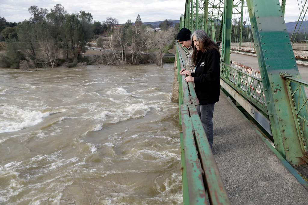 . Marcie Peterson, center right, watches the gushing waters from the Feather River next to her son Robert Baltierra, Wednesday, Feb. 15, 2017, in Oroville, Calif. Authorities say the immediate danger has passed and allowed people living downstream of the Oroville Dam to go back home Tuesday after ordering an evacuation Sunday. But, new storms forecast to hit Northern California this week will test quick repairs to the dam.  (AP Photo/Marcio Jose Sanchez)