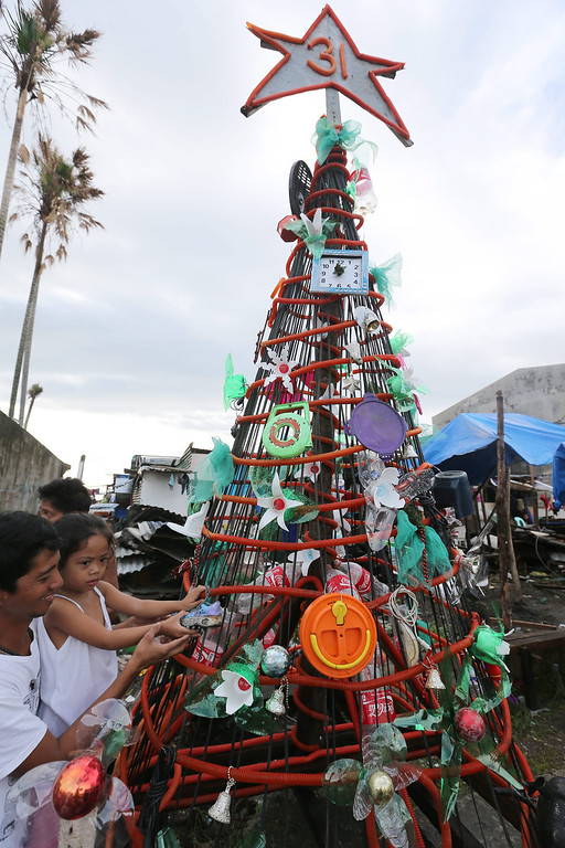 . Filipino typhoon survivors Alejandro Guande, 41, and her daughter Alia, 3, arrange a giant Christmas tree in preparation for traditional Christmas dinner \'Noche Buena\' outside a public school turned into a temporary evacuation center in the typhoon devastated city of Tacloban, Leyte Province, Philippines, 24 December 2013. Town officials have launched a contest for the best Christmas decoration among the villages in the city of Tacloban, with a first prize of some 1694 euros. The destruction and losses in lives and properties caused by Haiyan are casting a pall over the holiday season, in a country known for having the world\'s longest celebration of Christmas. According to the Philippine disaster relief agency, 6,102 people were killed and 1,779 were still missing from Haiyan\'s onslaught. The typhoon, the world\'s strongest on record, destroyed more than 1 million homes, key infrastructure and commercial establishments.  EPA/DENNIS M. SABANGAN