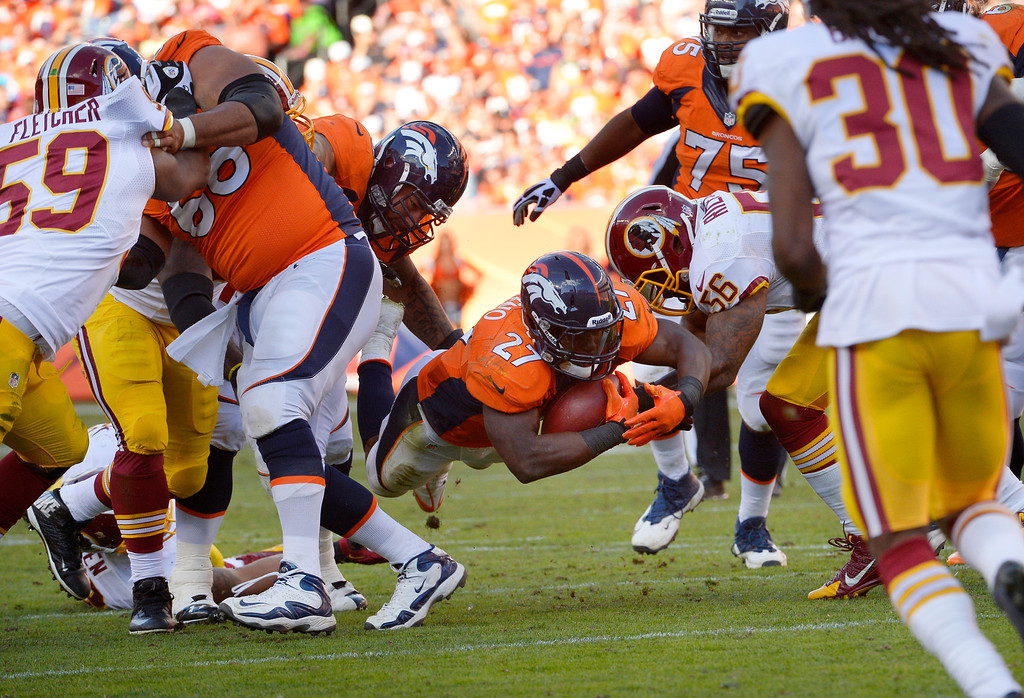. Denver Broncos running back Knowshon Moreno (27) dives through the hole for a first down in the third quarter.   (Photo by Joe Amon/The Denver Post)