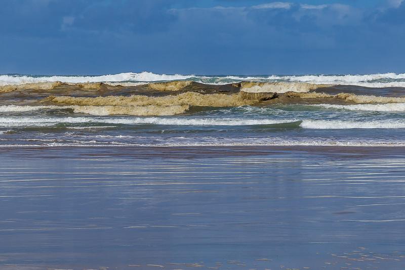 Wellen voller Sand an der Baylys Beach