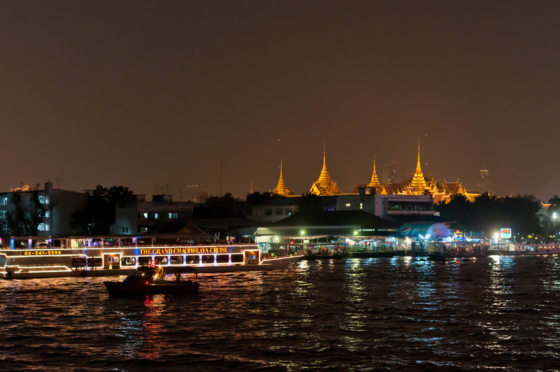 Bright skyline lights at night being reflected on the river - Thailand