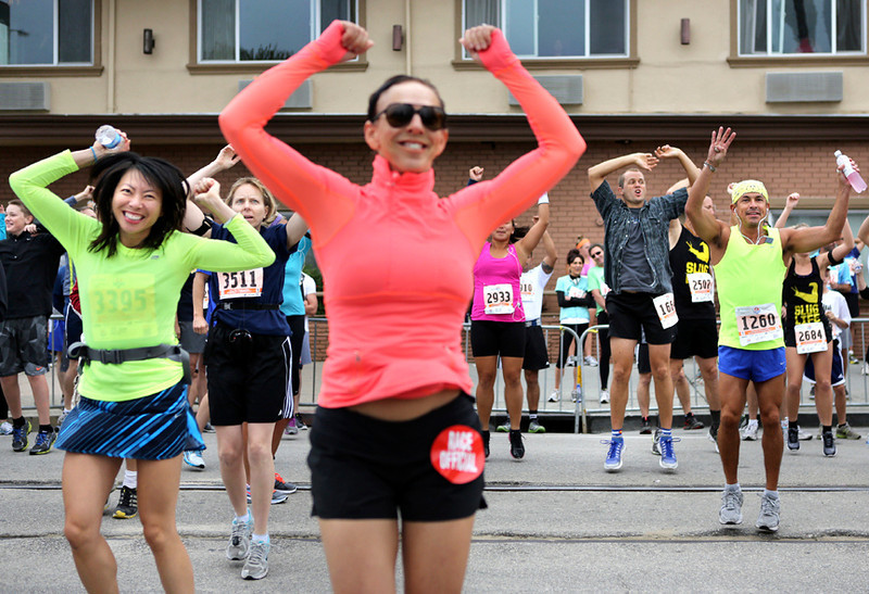 . Runners warm up by dancing along Beach Street in Santa Cruz on Sunday morning before the start of the 2013 Wharf to Wharf race. (Kevin Johnson/Sentinel)