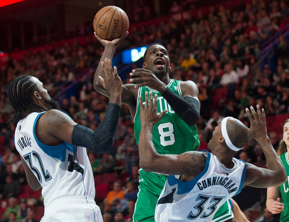 . Boston Celtics\' Jeff Green, center, takes a shot as Minnesota Timberwolves\' Ronny Turiaf, left, and Dante Cunningham, bottom right, defend during the first quarter. (AP Photo/The Canadian Press, Graham Hughes)