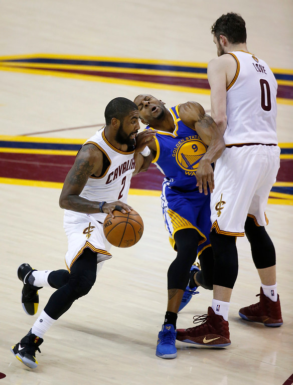 . Cleveland Cavaliers guard Kyrie Irving (2) drives as Golden State Warriors forward Andre Iguodala (9) runs into a screen by Cavaliers forward Kevin Love (0) during the first half of Game 3 of basketball\'s NBA Finals in Cleveland, Wednesday, June 7, 2017. (AP Photo/Ron Schwane)