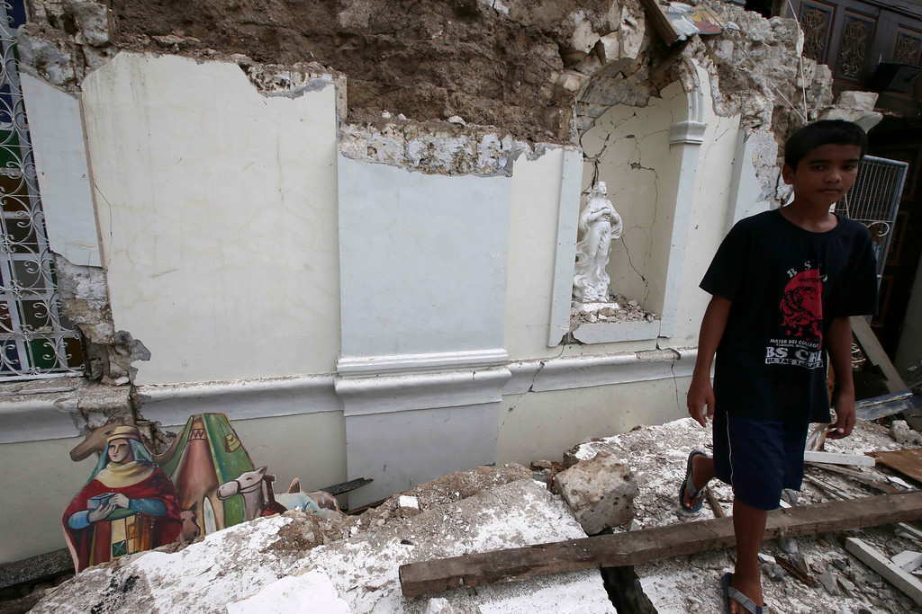 . A boy walks away from the rubble of San Isidro de Labrador church which was caused by a 7.2-magnitude earthquake  at Tubigon  township, Bohol province in central Philippines Wednesday Oct. 16, 2013.  (AP Photo/Bullit Marquez)