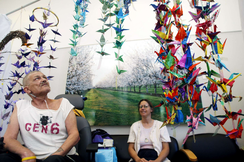 "Lung cancer patient Peter Myers(left) and colon cancer survivor Cindy Myers take a look at the hundreds of origami cranes hanging from the cieling in the hallways, some of which are for sale to raise money at Enloe Cancer Center Thursday afternoon. Peter said he'd thought anything to raise money for cancer is good, people forget ""cancer has to be fed with nutrition too. People have to eat."" - Halley photo 7/14/05"