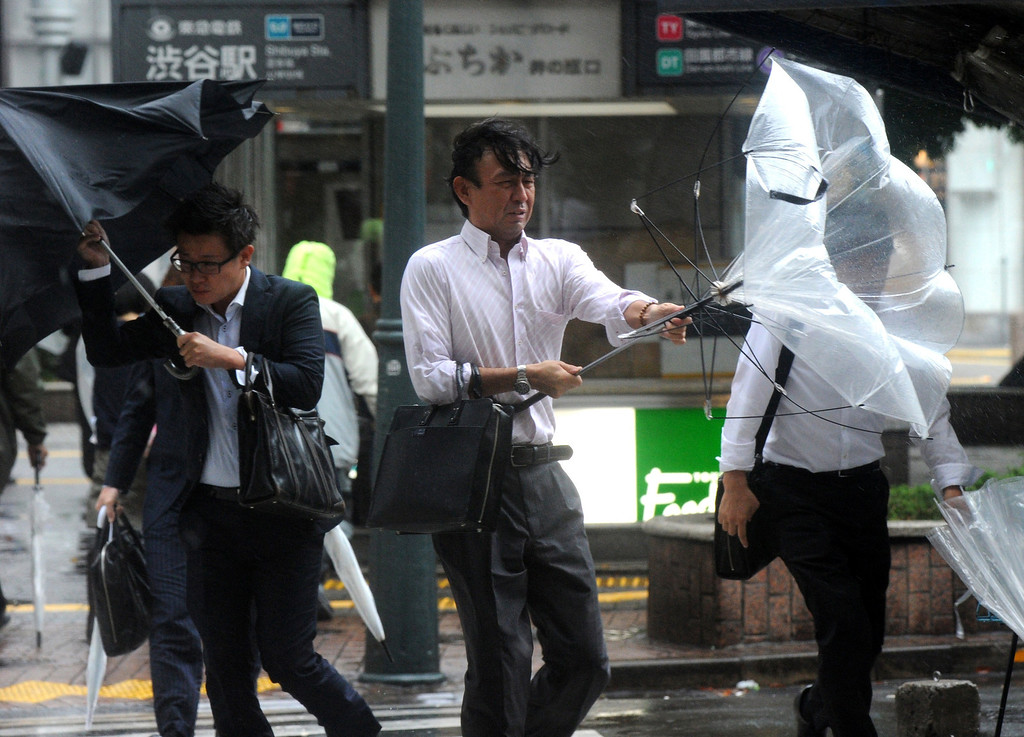 ". Japanese businessmen walk against strong wind and rain in Tokyo on October 16, 2013. At least three people died as Typhoon Wipha, the ""strongest in 10 years\"", passed close to Tokyo, causing landslides that swallowed houses on a Japanese island.  AFP PHOTO / Yoshikazu TSUNO/AFP/Getty Images"