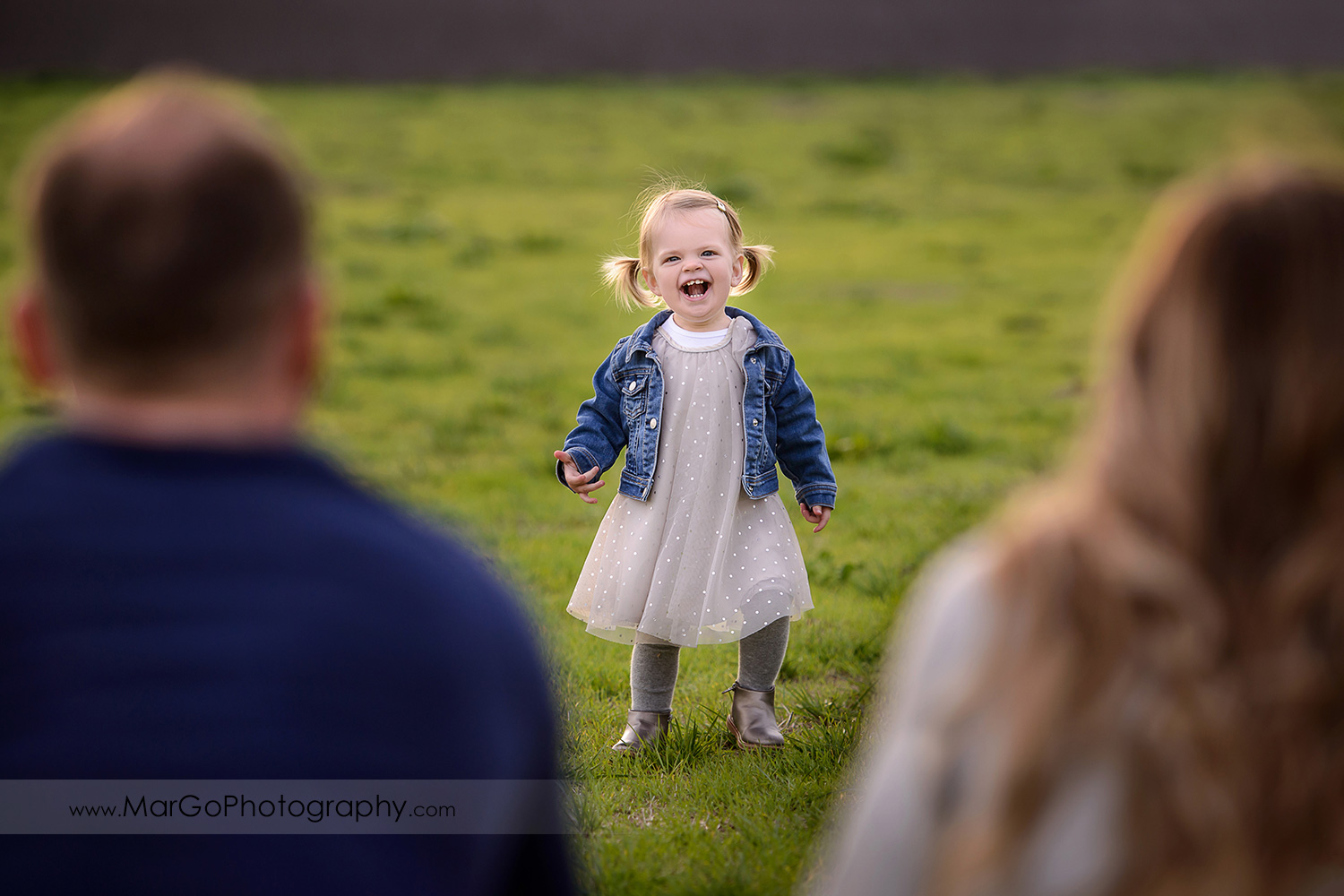little girl in white dress and jeans jacket through mother in white blouse and father wearing navy blue sweater during family session at San Jose Martial Cottle Park