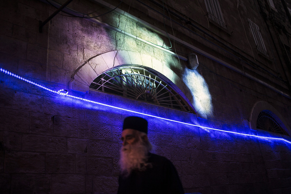 . JERUSALEM, ISRAEL - JUNE 5:  A visitor passes by a light installation during the annual Jerusalem Festival of Light on June 5, 2013 in Jerusalem, Israel. During the festival light installations are projected onto the historic buildings of Jerusalem\'s Old City.  (Photo by Ilia Yefimovich/Getty Images)
