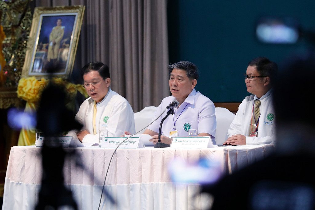 . Jesada Chokdumrongsuk, center, deputy director-general of the Public Health Ministry, speaks during a press conference at a hospital in Chiang Rai province, northern Thailand, Tuesday, July 10, 2018. Thai health official says rescued boys will be staying in hospital at least seven days. The Thai public health official said the eight boys rescued from a flooded cave in northern Thailand are in �high spirits� and have strong immune systems because they are soccer players. (AP Photo/Vincent Thian)