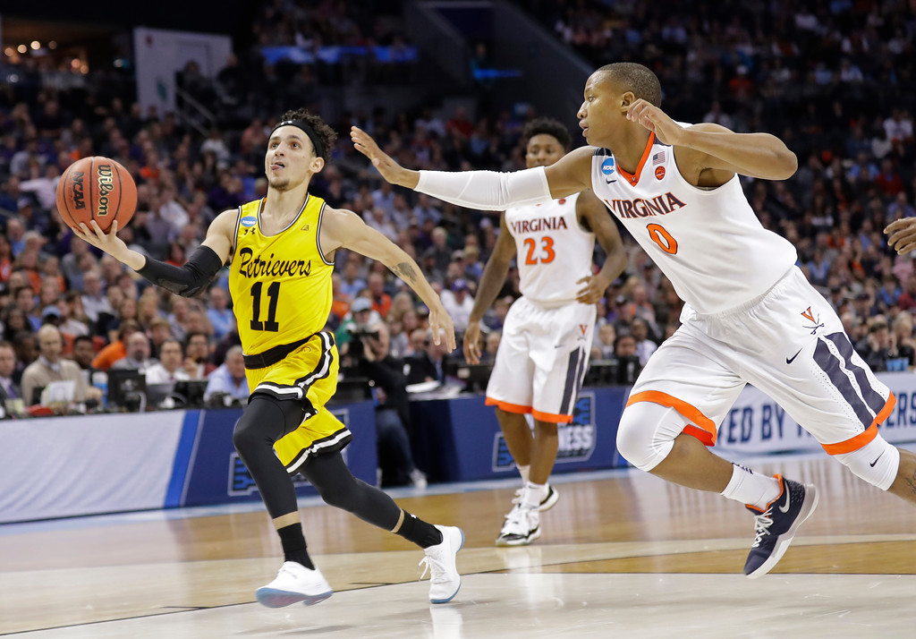 . UMBC\'s K.J. Maura (11) drives past Virginia\'s Devon Hall (0) during the second half of a first-round game in the NCAA men\'s college basketball tournament in Charlotte, N.C., Friday, March 16, 2018. (AP Photo/Gerry Broome)