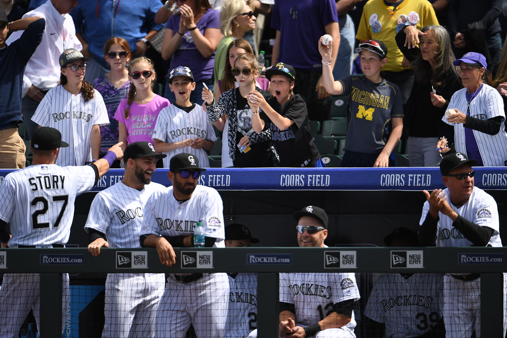 . Trevor Story (27), at left, of the Colorado Rockies tosses an autographed baseball to a fan before the game. The Colorado Rockies played the San Diego Padres Friday, April 8, 2016 on opening day at Coors Field in Denver, Colorado. (Photo By RJ Sangosti/The Denver Post)