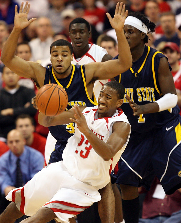 . Ohio State\'s David Lighty (23) passes as he falls to the floor as Kent State\'s Julian Sullinger, left, Haminn quaintance (1) defend during the first half of the BCA classic basketball game, Sunday, Nov. 12, 2006, in Columbus, Ohio. Ohio State foward Othello Hunter in the background. (AP Photo/Terry Gilliam)