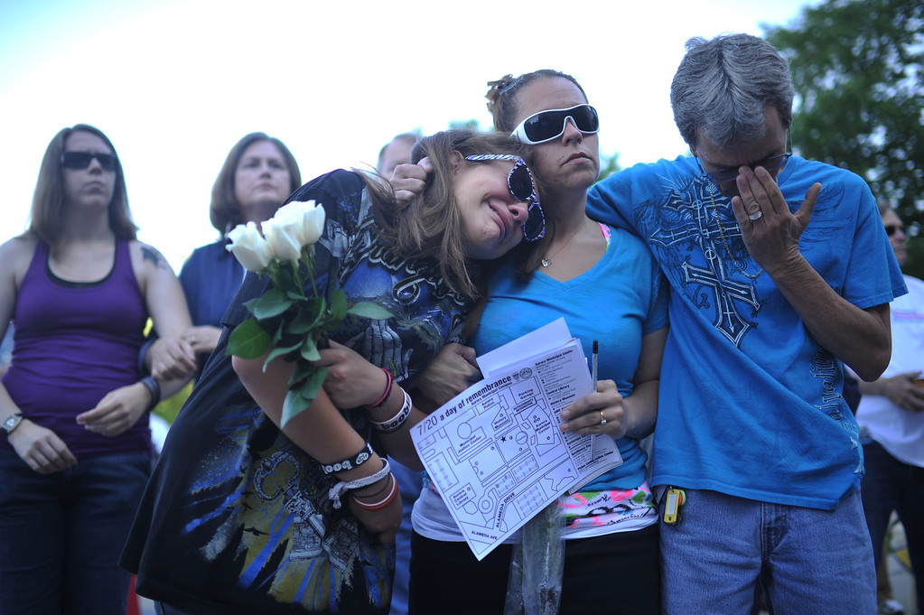 . AURORA, CO. - July 20: From font left, friend of aurora theater shooting victim Jessica Ghawi, Jasmine Christman and her parents Yulanda Vega Jordan and Jack Jordan comfort each other during a day of remembrance at Aurora Municipal Center. Aurora, Colorado. July 20, 2013. People gathered outside the Aurora Municipal Center to mark the first anniversary of the deaths of 12 people and the injury of at least 70 others in a mass shooting that forever changed an entire community. (Photo By Hyoung Chang/The Denver Post)