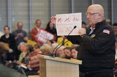 Larry Brown hold up a diagram of Boeing commercial airlines during his public testimony to the City Council at Seattle City Hall in Seattle, Washington on March 30, 2015.