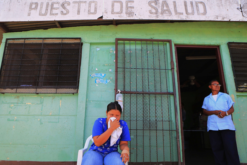 . Twenty-seven-year-old Valeria Garcia (C), waits to be treated for dengue fever, outside the Cristo del Rosario health centre in Managua, on October 25, 2013. The Nicaraguan government issued a health red alert as a dengue fever epidemic has killed 13 people so far this year - six in the past week - and infected more than 4,000 individuals, according to presidential spokesman Rosario Murillo. Dengue, transmitted by the Aedes aegypti mosquito, occurs in Central America mostly during its rainy season from May to November. The disease causes fever, muscle and joint ache as well as potentially fatal dengue hemorrhagic fever and dengue shock syndrome. Inti Ocon/AFP/Getty Images