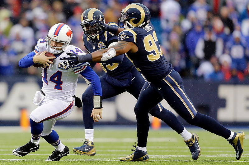 . Buffalo Bills quarterback Ryan Fitzpatrick (14) runs with the ball as St. Louis Rams\' William Hayes, center, and Eugene Sims give chase during the second half of an NFL football game, Sunday, Dec. 9, 2012, in Orchard Park, N.Y. (AP Photo/Gary Wiepert)