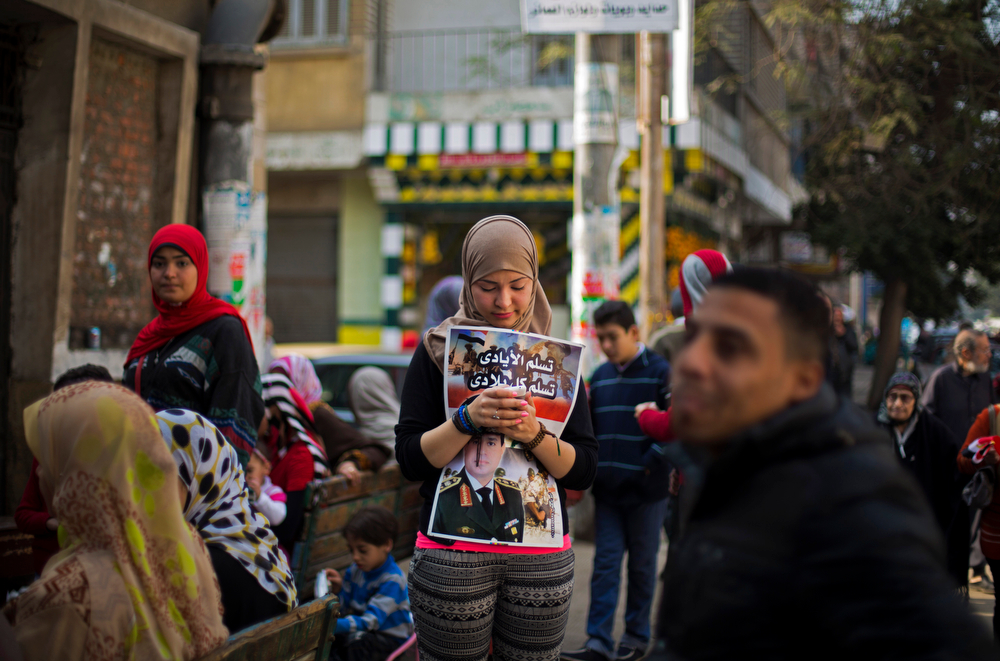 ". An Egyptian woman holds a poster with a picture of Egypt\'s Defense Minister, Gen. Abdel-Fattah el-Sissi, as she waits to vote in the country\'s constitutional referendum in Cairo, Egypt, Tuesday, Jan. 14, 2014. Upbeat and resentful of the Muslim Brotherhood, Egyptians voted Tuesday on a new constitution in a referendum that will pave the way for a likely presidential run by the nation\'s top general months after he ousted Islamist President Mohammed Morsi. Arabic on the poster reads, ""blessed be the hands may my entire homeland be safe.\"" (AP Photo/Khalil Hamra)"