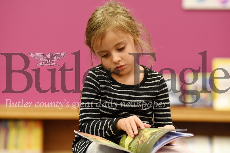 Harold Aughton/Butler Eagle: Audrey Fellers, 4, of Mars leafs through a children's book at the Mars Library with her mother, Vanessa Fellers, Monday, Dec. 9, 2019.