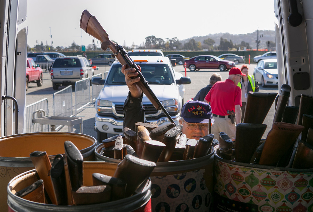 . Sheriff Deputy Wayne Ross puts a rifle away that were turned in during an anonymous gun buyback at the San Mateo County Event Center. (John Green/Staff)