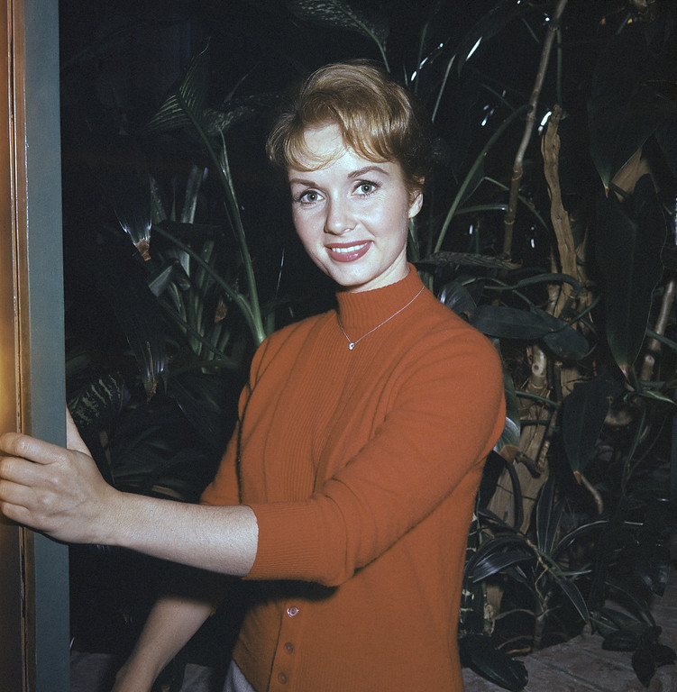. Actress Debbie Reynolds wears red and gray outfit, as seen at home Los Angeles, California on June 9, 1960. (AP Photo)
