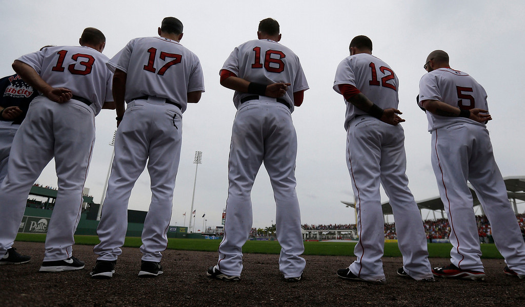 . Boston Red Sox stand for the National Anthem before an exhibition baseball game against the Minnesota Twins in Fort Myers, Fla., Saturday, March 29, 2014. (AP Photo/Gerald Herbert)