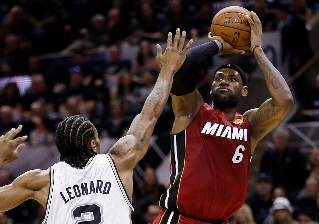 . Miami Heat forward LeBron James (6) shoots over San Antonio Spurs forward Kawhi Leonard (2) during the first half in Game 1 of the NBA basketball finals on Thursday, June 5, 2014, in San Antonio. (AP Photo/Eric Gay)