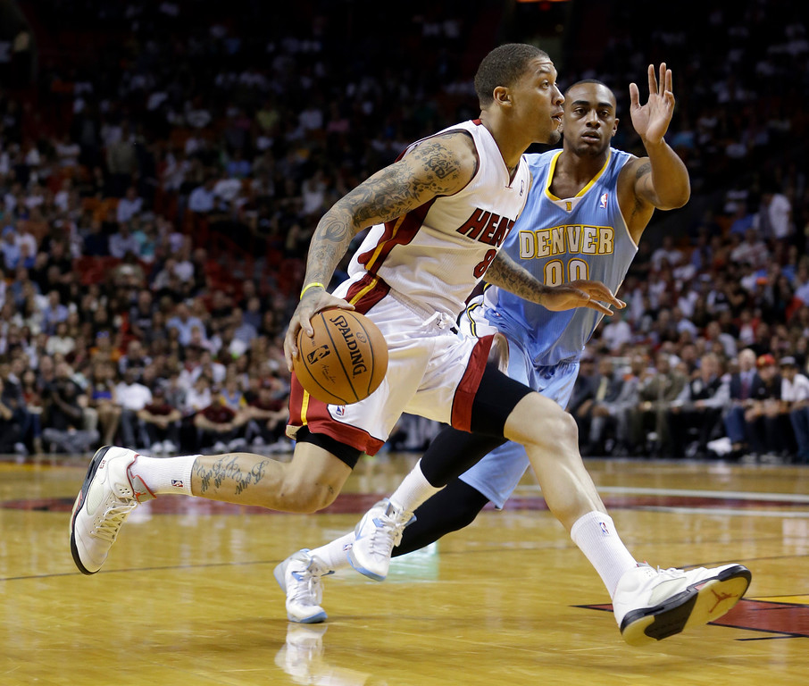 . Miami Heat forward Michael Beasley (8) drives around Denver Nuggets forward Darrell Arthur (00) during the first half of an NBA basketball game in Miami, Friday, March 14, 2014. (AP Photo/Alan Diaz)