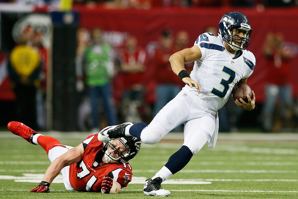 Description of . Russell Wilson #3 of the Seattle Seahawks escapes the tackle of  Kroy Biermann #71 of the Atlanta Falcons in the second quarter of the NFC Divisional Playoff Game at Georgia Dome on January 13, 2013 in Atlanta, Georgia.  (Photo by Kevin C. Cox/Getty Images)