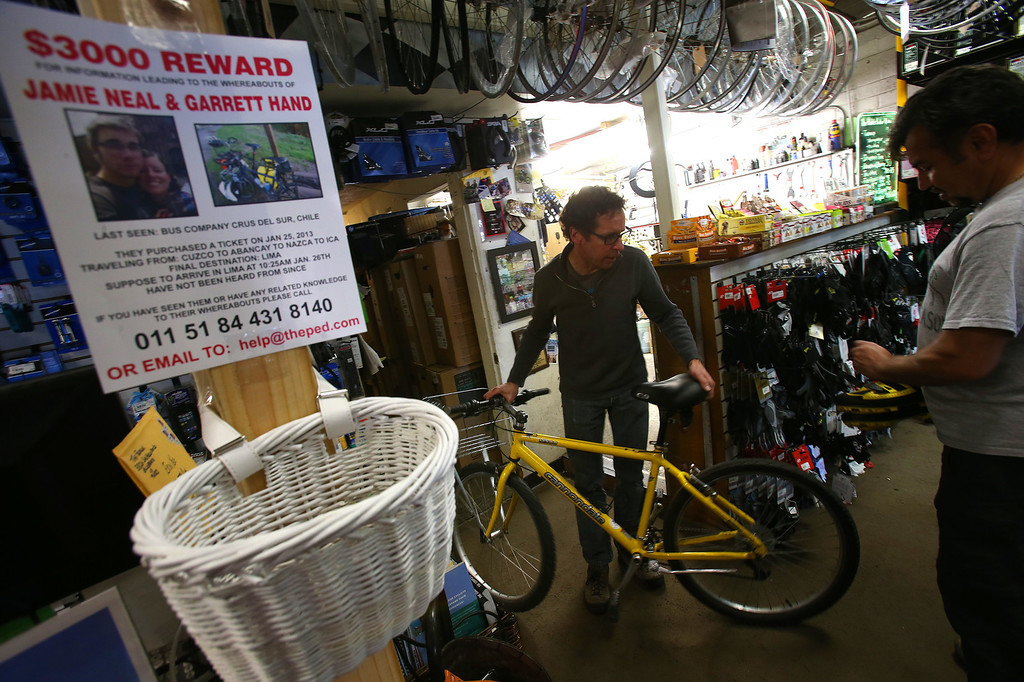 . Ron Hammer, center, of The Pedaler Bike Shop, helps customers on Sunday, Feb. 24, 2013, in El Sobrante, Calif.  Jamie Neal, a worker at the bike shop, and her boyfriend Garrett Hand were supposed to arrive in Lima, Peru, on Jan. 26 and have been reported as missing.  The store has made up missing person fliers to pass out at the shop.   (Aric Crabb/Staff)