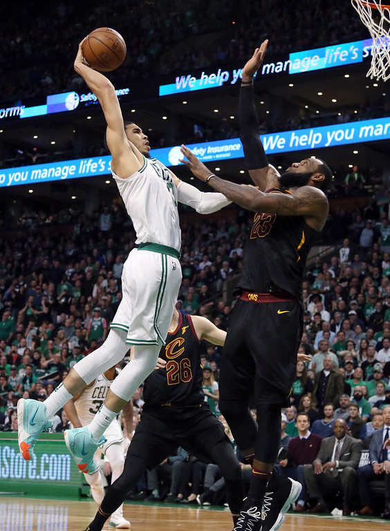 . Boston Celtics forward Jayson Tatum, left, goes up for a dunk against Cleveland Cavaliers forward LeBron James during the second half in Game 7 of the NBA basketball Eastern Conference finals, Sunday, May 27, 2018, in Boston. (AP Photo/Elise Amendola)