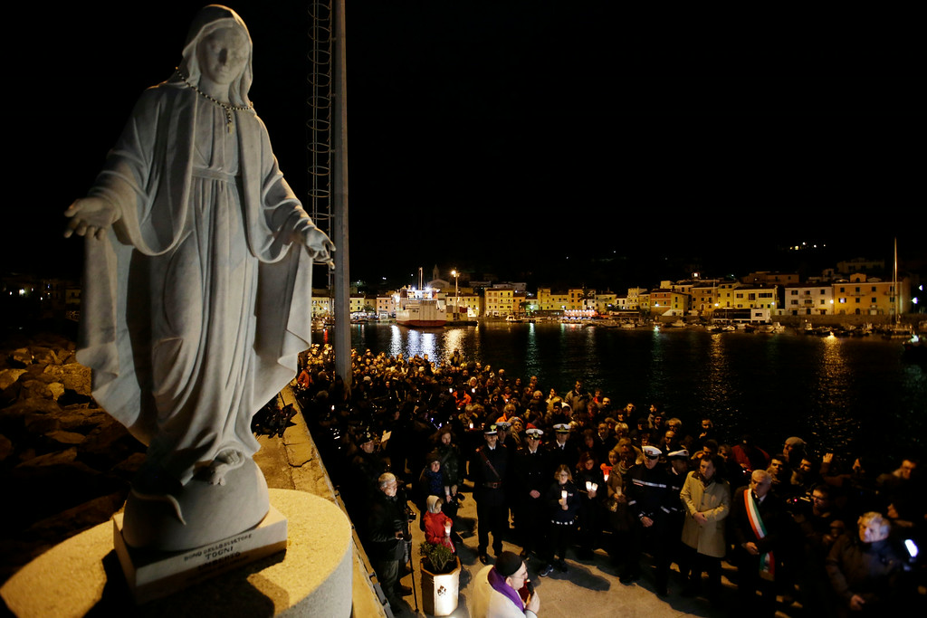 . People pray in front of a commemorative plaque bearing the names of the 32 victims of the Costa Concordia shipwreck, on the Tuscan Island of Giglio, Italy, Monday, Jan. 13, 2014. Survivors of the Costa Concordia\'s collision and capsizing marked the second anniversary Monday of the shipwreck in which 32 people perished with a candlelight march and the wail of sirens on the tiny Tuscan island where they came to safety, and with a moment of silence in the courtroom where the luxury liner\'s captain is on trial for manslaughter. (AP Photo/Gregorio Borgia)