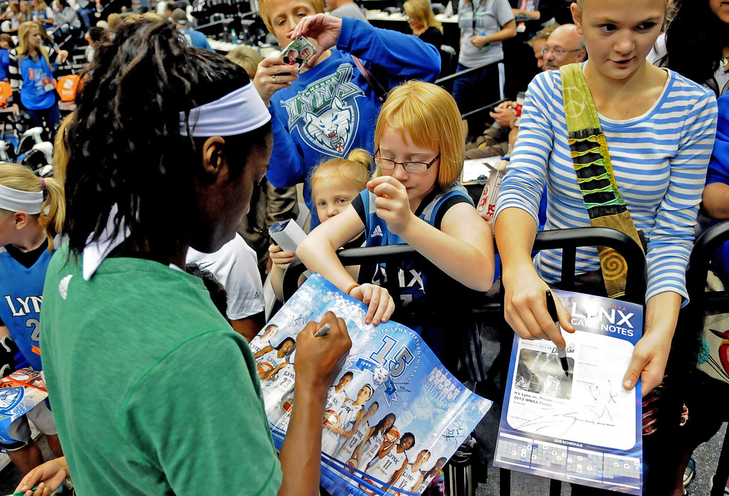 . Minnesota\'s Devereaux Peters signs autographs for Grace Roesch, 8, center, while mom Julie Roesch, top, takes a photo before the game. (Pioneer Press: Sherri LaRose-Chiglo)