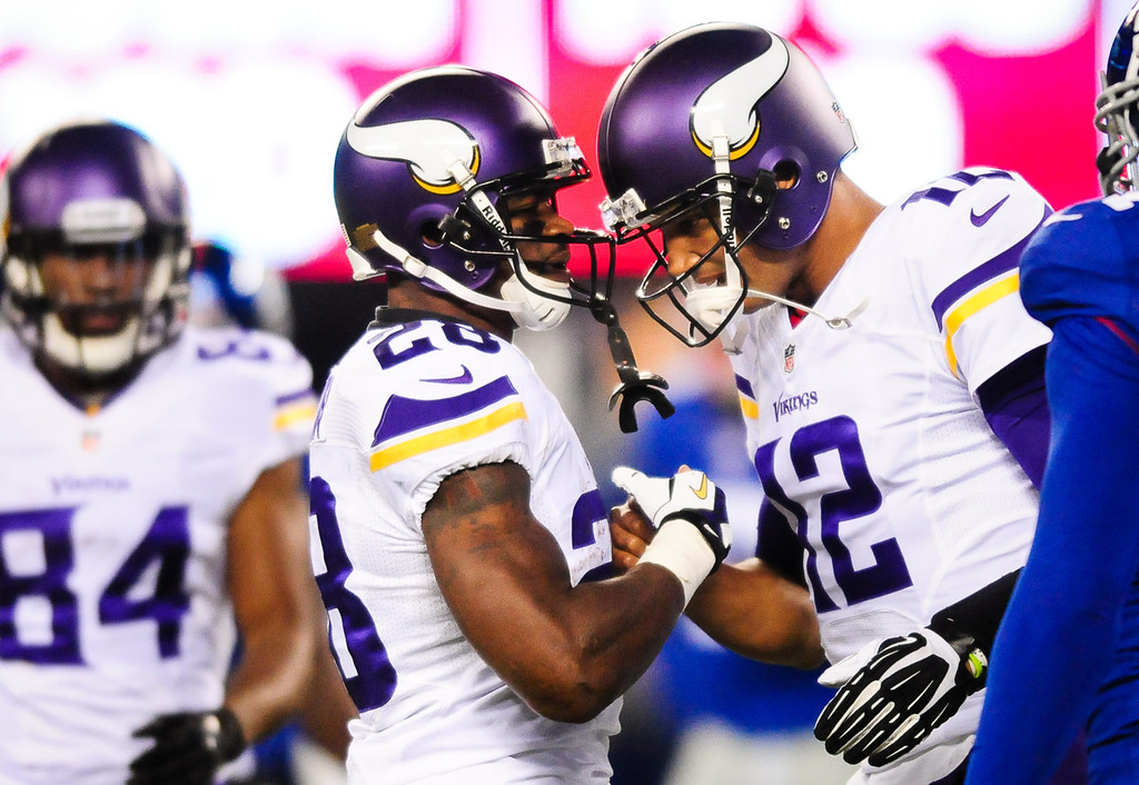 . Vikings running back Adrian Peterson, left, and quarterback Josh Freeman  greet each other after Freeman overthrew Peterson on a pass in the second quarter against the Giants.  (Pioneer Press: Ben Garvin)