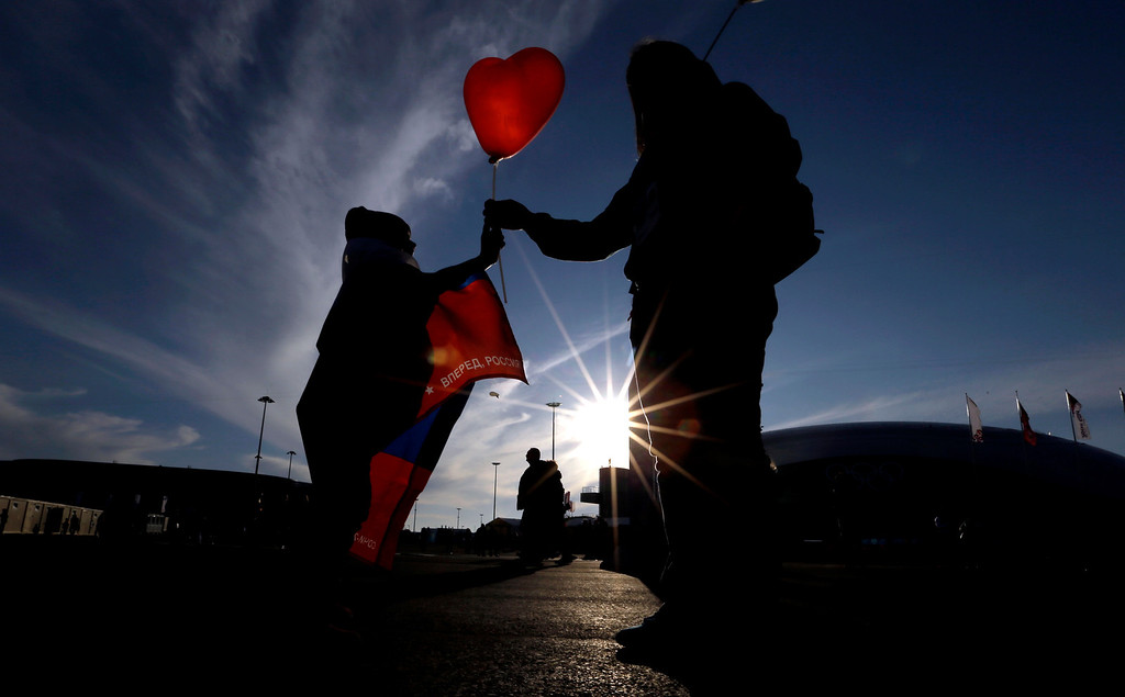 . An Olympic volunteer, right, hands a heart-shaped balloon to a child visiting Olympic Park on Valentine\'s Day at the 2014 Winter Olympics, Friday, Feb. 14, 2014, in Sochi, Russia. (AP Photo/David J. Phillip )