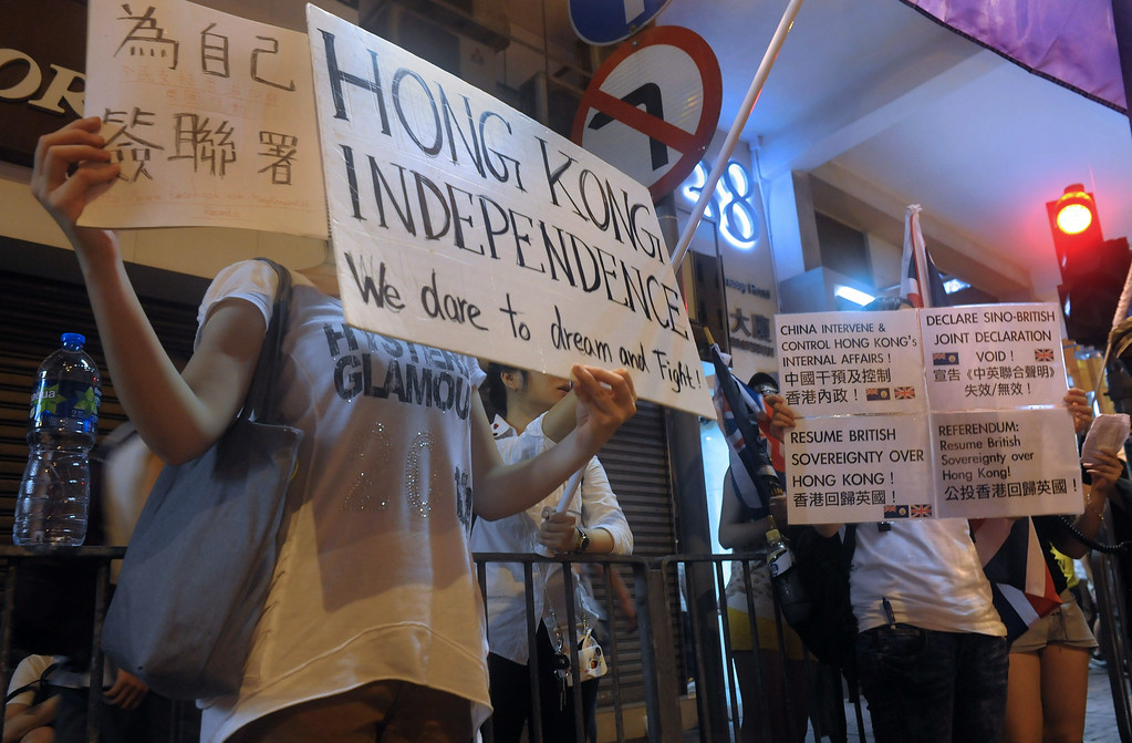 ". Protesters hold up pro-independence placards while hundreds of thousands take part in a pro-democracy rally seeking greater democracy in Hong Kong on July 1, 2014 as frustration grows over the influence of Beijing on the city.  July 1 is traditionally a day of protest in Hong Kong and also marks the anniversary of the handover from Britain to China in 1997, under a ""one country, two systems\"" agreement.      RICHARD A. BROOKS/AFP/Getty Images"