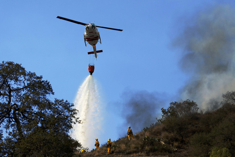 . Helicopters drop water on the wildfires as they burn through the hillsides on January 16, 2014 in Glendora, California. A wildfire near Glendora in the San Gabriel Valley has prompted officials to order evacuations for houses near the fire.  (Photo by Dan R. Krauss/Getty Images)