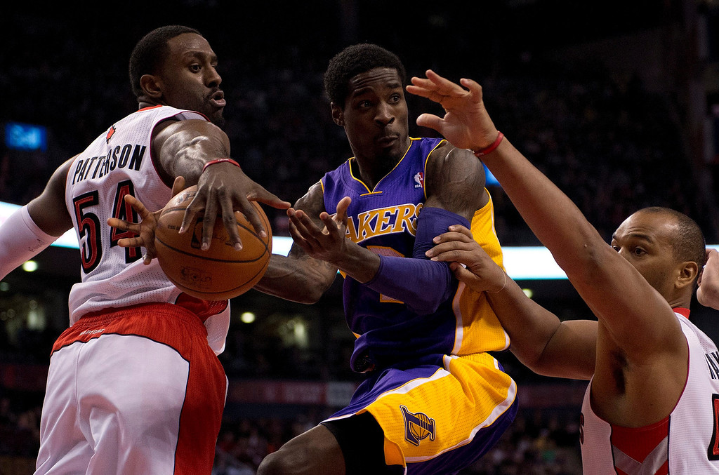 . Los Angeles Lakers guard Manny Harris, center, has the ball stripped as the tries to pass while driving between Toronto Raptors forwards Patrick Patterson (54) and Chuck Hayes, right, during first-half NBA basketball game action in Toronto, Sunday, Jan. 19, 2014. (AP Photo/The Canadian Press, Frank Gunn)